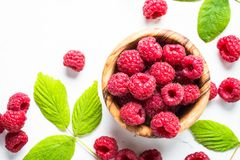 Fresh raspberries in wooden bowl on white table. Top view Stock Photos