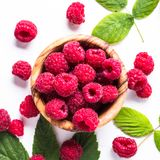 Fresh raspberries in wooden bowl on white table. Royalty Free Stock Images