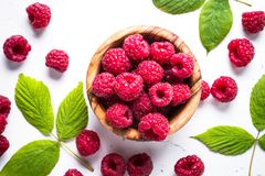 Fresh raspberries in wooden bowl on white table. Royalty Free Stock Photos