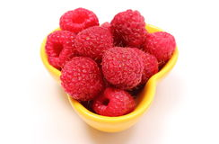 Fresh raspberries in yellow bowl on white background Stock Images