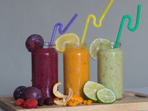 Fresh raspberry, banana, spinach and orange drinks on wooden table. Detox diet concept Royalty Free Stock Images