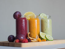 Fresh raspberry, banana, spinach and orange drinks on wooden table. Royalty Free Stock Photos