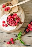 Fresh raspberry with basil in a cup of coffee and a wooden stand. Detox diet food and raw vegan concept Stock Photo