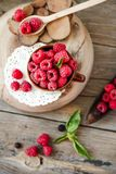 Fresh raspberry with basil in a cup of coffee and a wooden stand. Detox diet food and raw vegan concept. Top view Stock Images