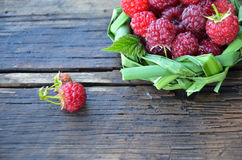 Fresh raspberry in a basket of leaves on wooden background Royalty Free Stock Photography