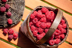 Fresh raspberry in a basket on wooden table. Sunlight Stock Photography