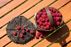 Fresh raspberry in a basket on wooden table. Sunlight Royalty Free Stock Photo
