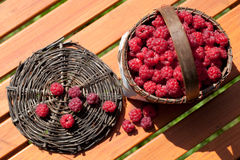 Fresh raspberry in a basket on wooden table Stock Photos