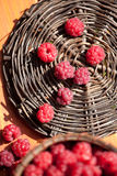 Fresh raspberry in a basket on wooden table. Sunlight Stock Photos
