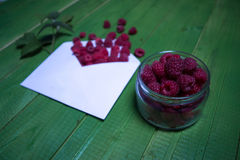 Fresh raspberry berries in an envelope on a green wooden background. Fresh raspberry berries in an envelope on a green wooden background Royalty Free Stock Photo