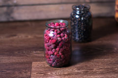 Fresh raspberry berries in a glass jar on a wooden background. Stock Photography