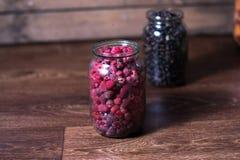 Fresh raspberry berries in a glass jar on a wooden background. Fresh raspberry berries in a glass jar on a wooden background Stock Photography