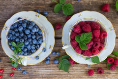 Fresh raspberry and blueberry. With green leaves in cups, top view Royalty Free Stock Photos