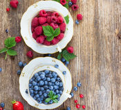 Fresh raspberry and blueberry. With green leaves in cups on wooden table, top view Stock Image