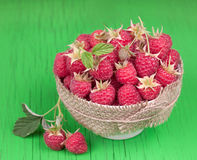 Fresh raspberry  in bowl. On green wooden surface Stock Images
