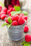 Fresh raspberry in the bucket. On the wooden table Stock Photos