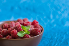 Fresh raspberry in ceramic bowl on the blue background Royalty Free Stock Photography