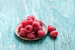 Fresh raspberry. In ceramic plate on the blue wooden rustic desk with copy space Stock Photo