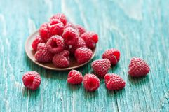 Fresh raspberry. In ceramic plate on the blue wooden rustic desk with copy space Stock Photos