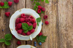 Fresh raspberry. In cup with green leaves on wooden background, top view Stock Image