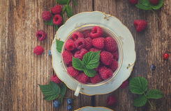 Fresh raspberry in cup. Raspberry in cup with green leaves on wooden background, top view, retro toned Stock Image