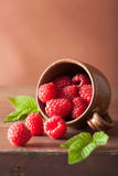 Fresh raspberry in cup over wooden background. Fresh raspberry in a cup over wooden background Royalty Free Stock Photo