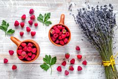 Fresh raspberry and dry lavander in rustic design wooden backgro. Fresh raspberry in pots and lavander dry flowers in rustic design on wooden background top view Royalty Free Stock Photos