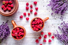 Fresh raspberry and dry lavander in rustic design wooden backgro. Fresh raspberry in pots and lavander dry flowers in rustic design on wooden background top view Stock Photography