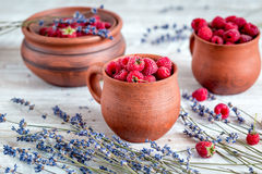 Fresh raspberry and dry lavander in rustic design on wooden background. Fresh raspberry in pots and lavander dry flowers in rustic design on wooden background Stock Images