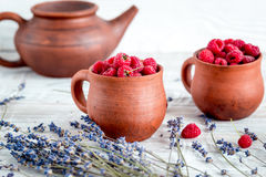 Fresh raspberry and dry lavander in rustic design on wooden background. Fresh raspberry in pots and lavander dry flowers in rustic design on wooden background Royalty Free Stock Photography
