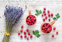 Fresh raspberry and dry lavander in rustic design wooden background top view. Fresh raspberry in pots and lavander dry flowers in rustic design on wooden Royalty Free Stock Photo