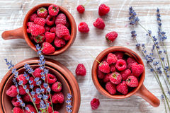 Fresh raspberry and dry lavander in rustic design wooden background top view. Fresh raspberry in pots and lavander dry flowers in rustic design on wooden Stock Photos