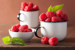 Fresh raspberry in enamel cups over wooden background Stock Photo