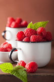 Fresh raspberry in enamel cups over wooden background Royalty Free Stock Photos