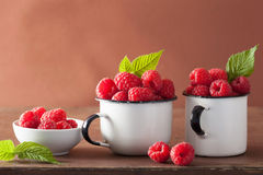 Fresh raspberry in enamel cups over wooden background.  Royalty Free Stock Images