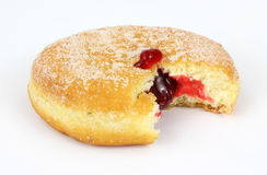 Fresh raspberry filled donut. A bitten freshly baked raspberry filled donut with sugar sprinkled on the surface Stock Photo