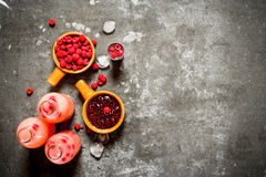 Fresh raspberry fruit drink with jam and ice. On the stone table Stock Photos
