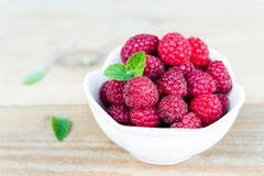 Fresh Raspberry Fruits In White Bowl on Wooden Table. Close-up of fresh raspberry fruits in a white bowl on wooden table with copy space Royalty Free Stock Images