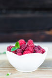 Fresh Raspberry Fruits In White Bowl on Wooden Table. Close-up of fresh raspberry fruits in a white bowl on wooden table with copy space Stock Photos