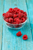 Fresh raspberry in a glasses bowl. On blue background Stock Image