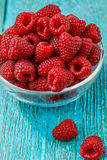 Fresh raspberry in a glasses bowl. On blue background Stock Images