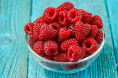 Fresh raspberry in a glasses bowl. On blue background Royalty Free Stock Photos
