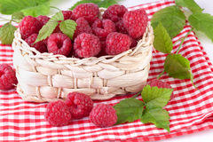 Fresh raspberry with green leaves. Fresh raspberries with leaves in basket Royalty Free Stock Photos