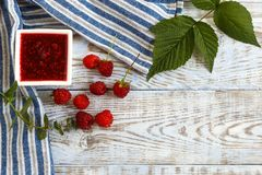 Fresh raspberry and raspberry jam on a light wooden background. Copy space Royalty Free Stock Image