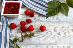 Fresh raspberry and raspberry jam on a light wooden background. Royalty Free Stock Photography