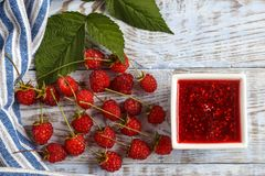 Fresh raspberry and raspberry jam on a wooden background. Raspberry and raspberry jam on white boards, top view Stock Photos