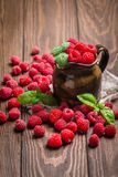 Fresh raspberry in a jug. On wooden background Royalty Free Stock Photography