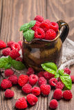 Fresh raspberry in a jug. On wooden background Stock Photography