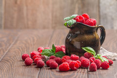 Fresh raspberry in a jug. On wooden background Stock Photos