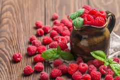 Fresh raspberry in a jug. On wooden background Royalty Free Stock Images